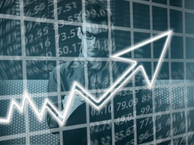 Car dealership competition - Image of business man with graph showing rising profits superimposed
