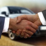 Customer retention strategies depend on relationships - image of two men's hands being shaken in front of grey car