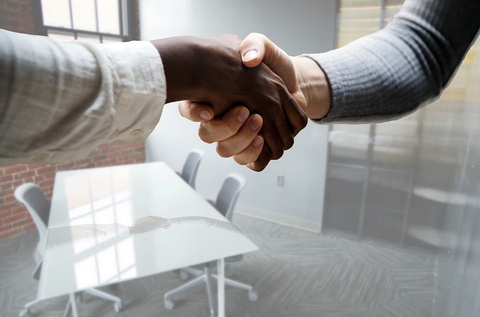 dealership sales team - white and black man shake hands over table