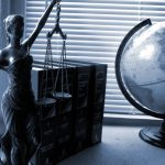 FTC Safeguards Rule changes may affect many dealerships - Image of law books, globe, and lady justice statue on desk