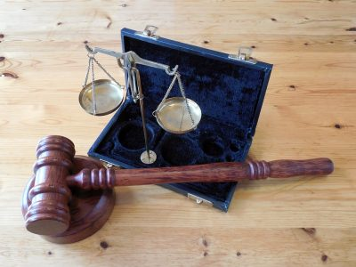 Auto dealership compliance can keep your dealership out of court - image of judge's gavel and scales on a wood table